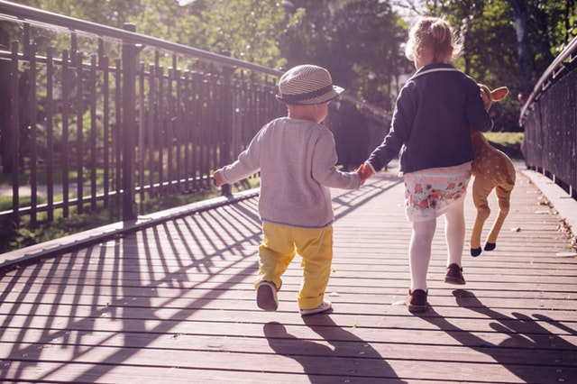 kluk s holčičkou běží přes most.jpg