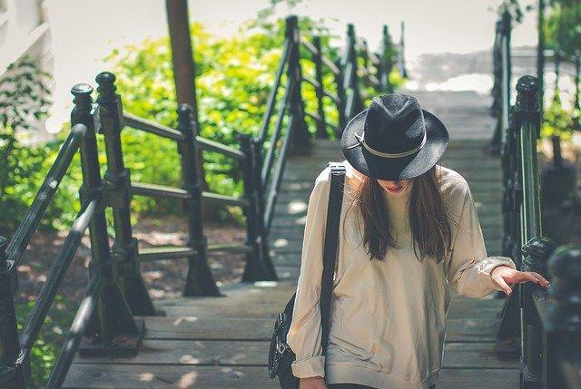 žena jdoucí po schodech s nerezovým zábradlím